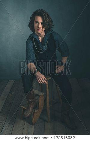 Vintage Alternative Artistic Fashion Man. Sitting On Wooden Stool In Studio.