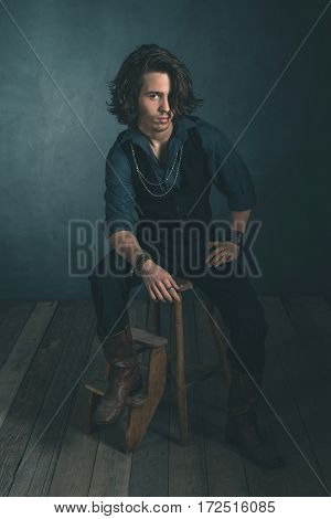 Vintage Alternative Artistic Fashion Man. Sitting On Wooden Stool In Studio.
