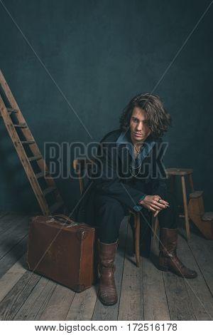 Alternative Artistic Vintage Man Wearing Black Coat. Smoking Cigarette. Sitting On Wooden Chair In S