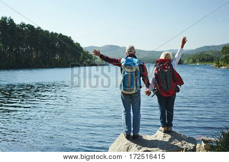 Adventurous seniors waving hands in front of lake