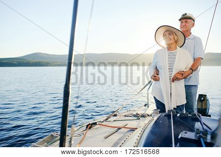Affectionate senior couple sailing on sunny day