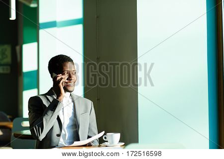 African-american trader speaking to client by cellphone
