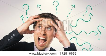 Close-up of frustrated businessman looking up against grey background