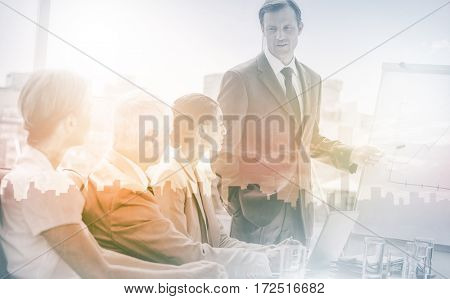 Businessman pointing at whiteboard during a meeting in front of attentive colleagues