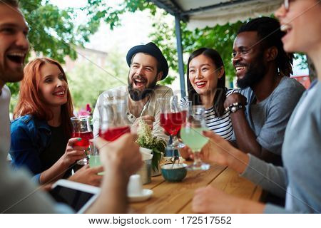 Laughing teenagers with drinks having rest in outdoor cafe