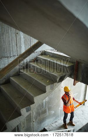 High angle view of construction worker wearing reflective orange vest and protective helmet standing using portable radio under unfinished flight of stairs among concrete walls