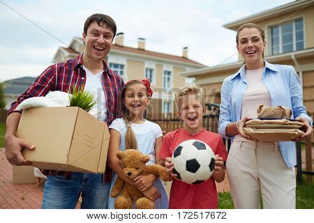 Portrait of happy family with two children, boy and girl, standing holding cardboard boxes and personal belongings outside, in front of their new house, smiling brightly, ready to move in