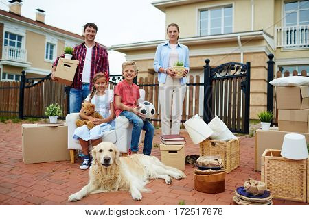 Portrait of happy family with two children and their golden retriever dog standing holding cardboard boxes