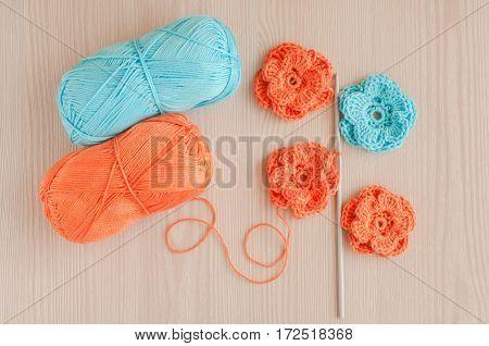 Handmade knitted crochet flowers. Needlework concept. Top view