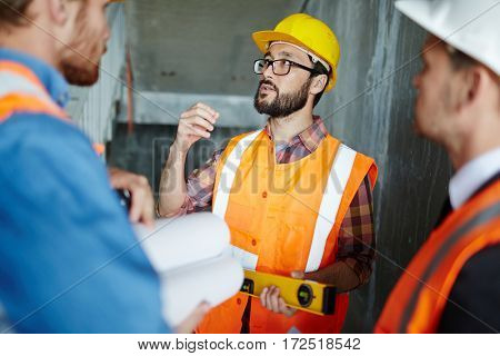 Portrait of bearded expert explaining construction details to workmen, making measurements as they go, all wearing reflective orange vests and hard hats