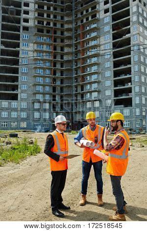 Group of three men wearing protective helmets and vests, one of them executive official, explaining project details to foreman on construction site against high-rise building