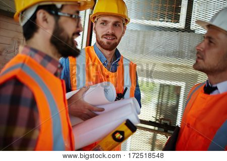 Group of three workmen wearing protective helmets and vests standing in elevator shaft on construction site discussing development progress, holding tools and blueprints