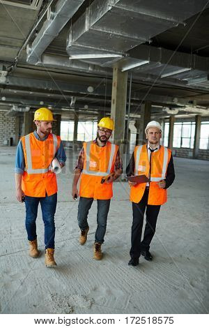 Group of three workmen wearing protective helmets and vests walking among concrete walls of unfinished building showing development progress to foreman inspector on construction site