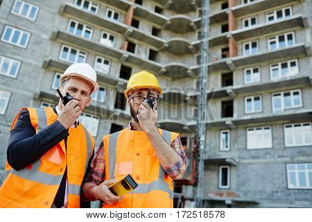 Portrait of two workmen wearing reflective orange vests and hard hats standing using portable radio sets against apartment building on construction site