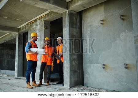 Two workmen showing unfinished floors in high rise building to executive supervisor on construction site, all wearing reflective orange vests and hard hats