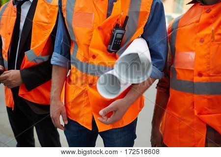 Closeup shot of three unrecognizable construction workers wearing orange reflective vests standing on site holding building plans