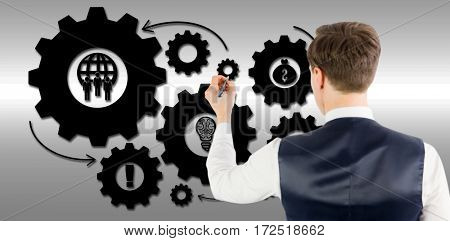 Businessman writing something with pen against grey background