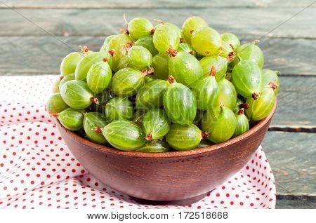 Fresh green gooseberries in a ceramic bowl on a napkin textile. Gooseberry close up. Rustic style