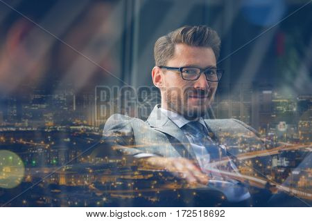 Portrait of handsome smiling businessman sitting in office