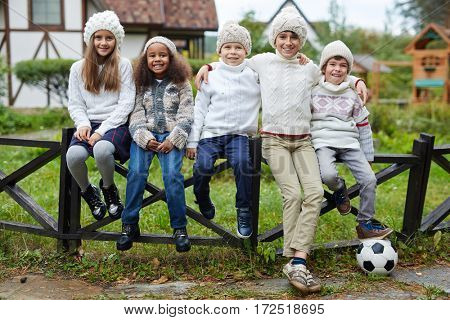Affectionate youngsters sitting in row outdoors