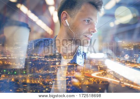 Handsome man listening music on mobile phone while holding coffee in train