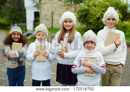 Cute youngsters with books standing in row outdoors