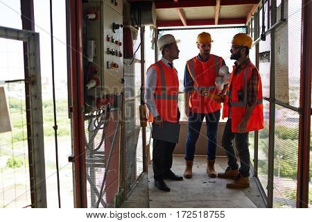 Group of workmen standing in industrial elevator discussing construction site progress, all wearing reflective orange vests and hard hats