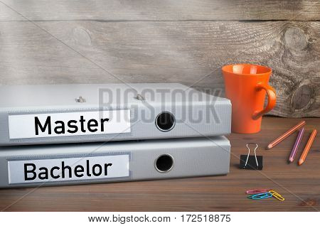 Bachelor and Master - two folders on wooden office desk.