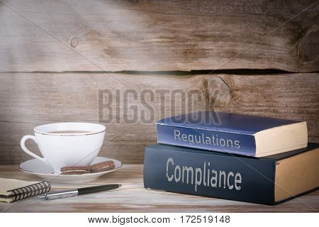 Compliance and Regulations. Stack of books on wooden desk.