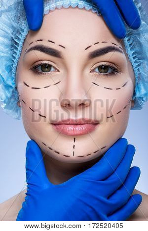 Pretty girl with dark eyebrows and nude make up at blue background, doctor's hands in blue gloves touching patient's face, plastic surgery, close up, perforation lines on face.