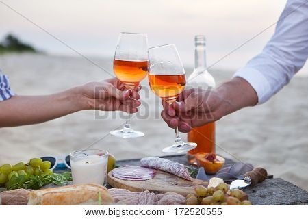 Man And Woman Clanging Wine Glasses With Rose Wine At Sunset Beach