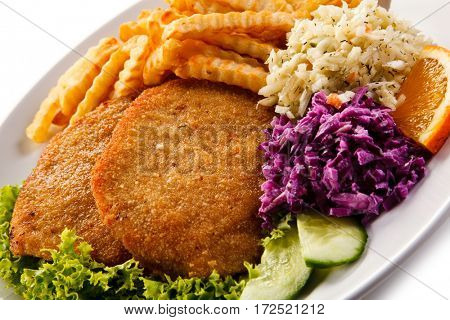 Fried pork chop, French fries and vegetables