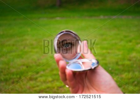 girl looking in a small mirror in her hand, in the frame only a hand mirror and eye