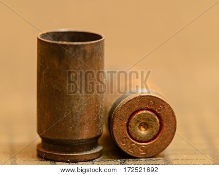 Empty 9mm bullet shell casings, on a wooden background