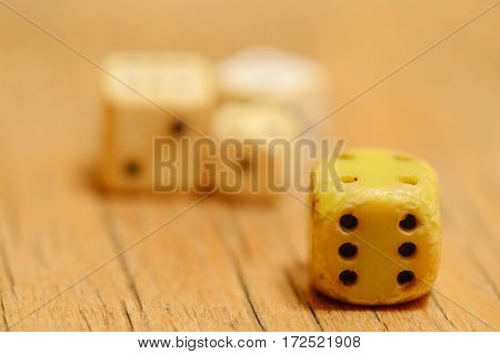 Rare dice on a wooden background four pieces