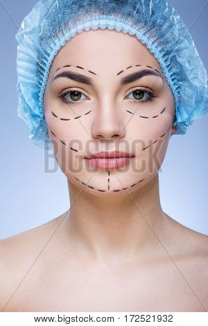Beautiful girl with dark eyebrows and naked shoulders wearing blue medical hat at blue background and looking at camera, plastic surgery, perforation lines on face.