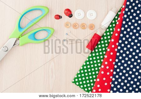 Polka dot fabric for sewing and accessories for needlework on wooden background. Spool of thread scissors buttons sewing supplies. Set for needlework top view