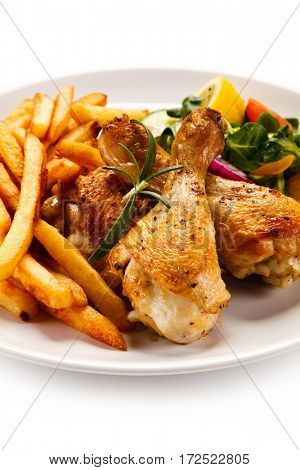 Grilled chicken legs with chips and vegetables