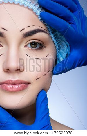 Attractive girl with dark eyebrows and nude make up at blue background, doctor's hands in blue gloves touching patient's face, plastic surgery, perforation lines on face.