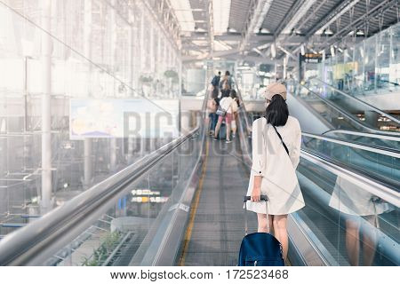 Beautiful young tourist girl with carry on luggage in international airport. woman on airport. airport in Bangkok. girl in airport. poster