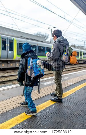 Travel concept of two boys on train station platform.