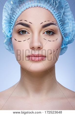 Close up portrait of girl with dark eyebrows and naked shoulders wearing blue medical hat at blue background and looking at camera, plastic surgery, perforation lines on face.