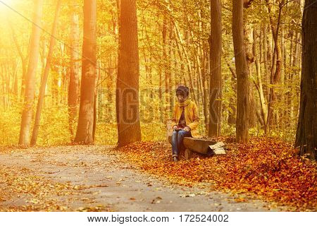 Young stylish hipster girl sitting on the bench in the autumn sunny park and reading electronic book