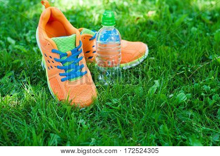 Sports shoes sneakers and bottle of water on a fresh green grass. The sun's rays. Sports outdoor