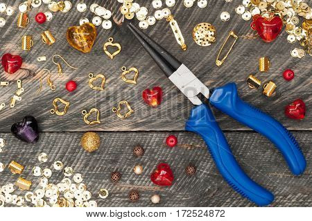 Tools for handmade jewelry. Beads plier glass hearts and accessories to create hand made jewelry on old wooden background. Top view