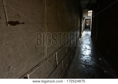Dark alleyway with a black door beyond