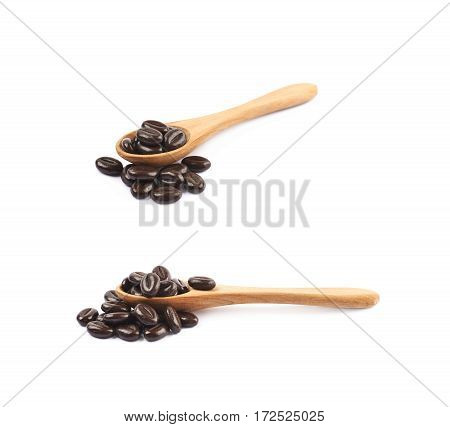 Pile of coffee bean shaped chocolate candies with a wooden spoon over it, composition isolated over the white background, set of two different foreshortenings