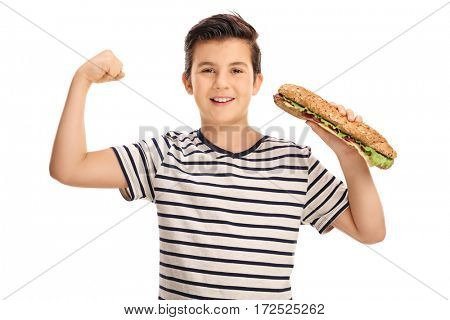 Young boy flexing his biceps and holding a sandwich isolated on white background