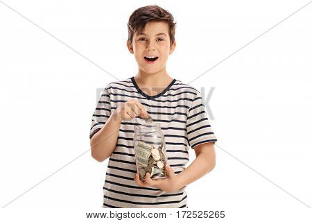 Joyful boy putting a coin into a jar with money isolated on white background