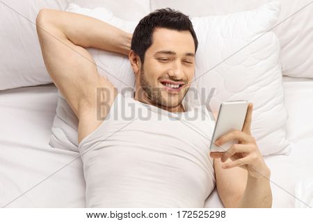 Young guy lying on a pillow and looking at a phone